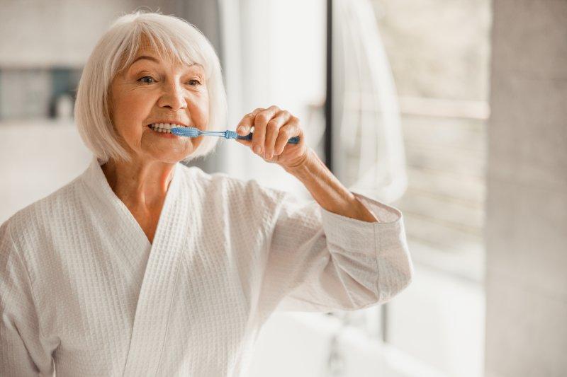 Older woman in white robe brushing teeth in bathroom